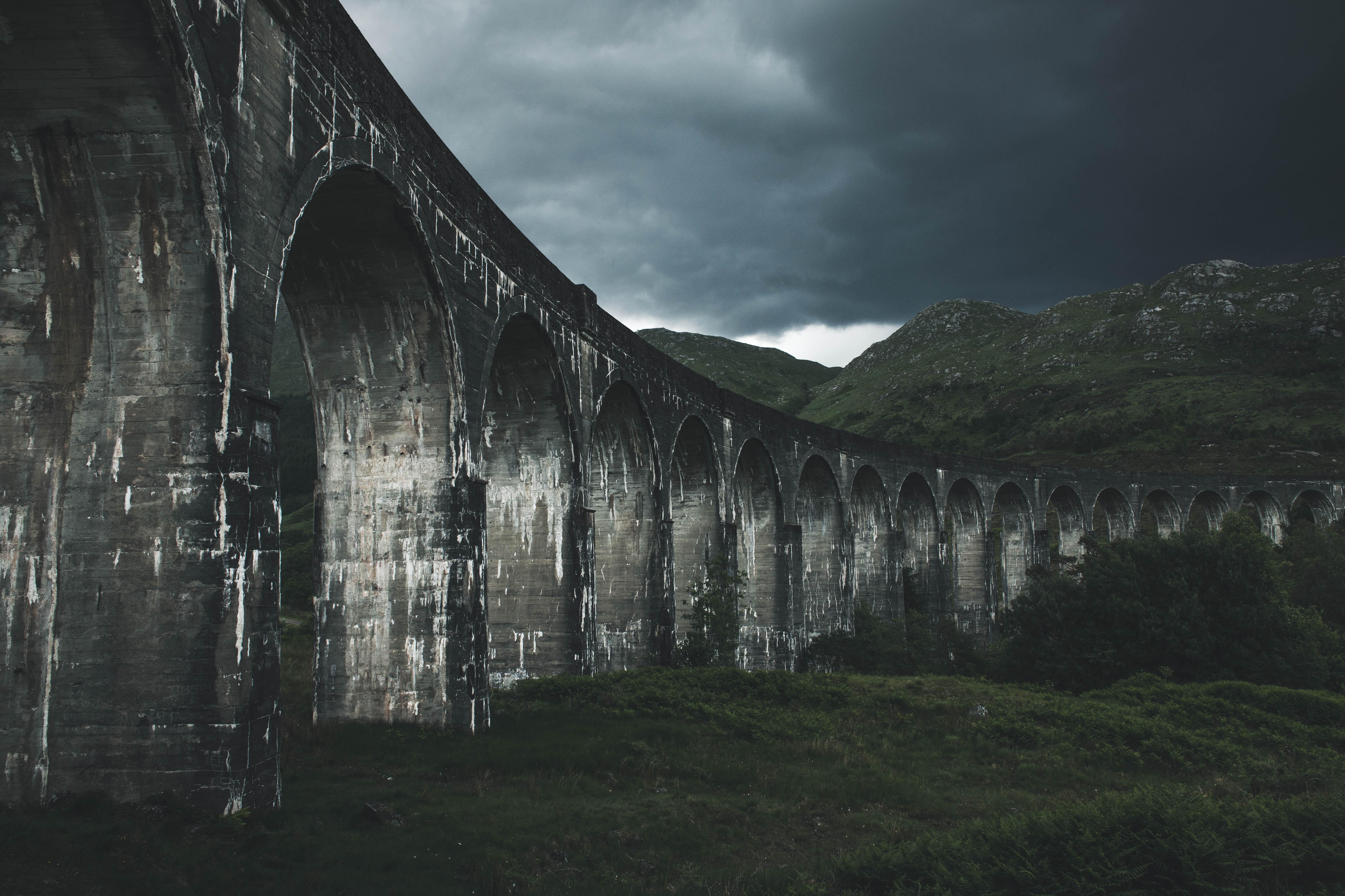 grey concrete bridge near hills