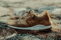 unpaired brown and white New Balance athletic shoe on ground