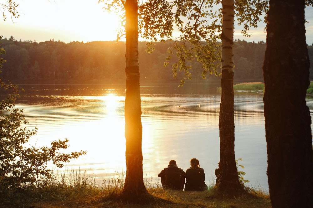 man and woman sitting near body of water during sunset