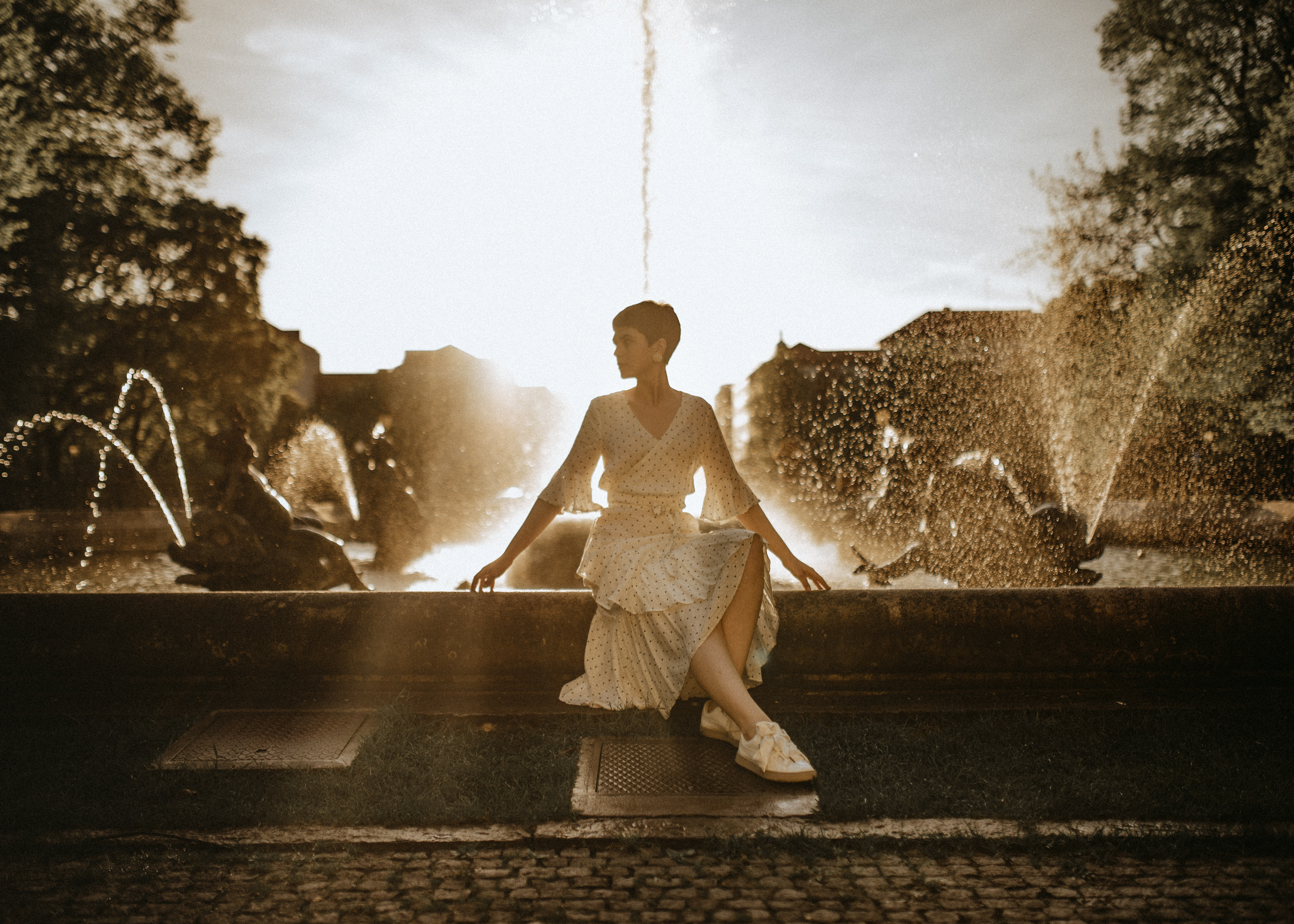 woman wearing white dress sitting near water fountain