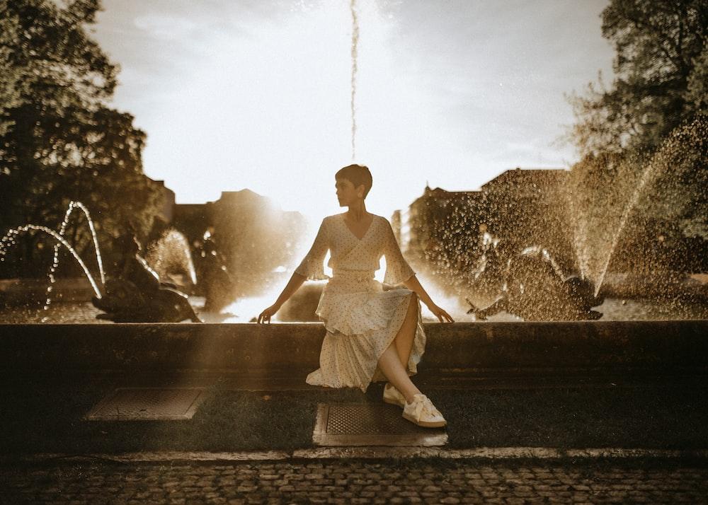 woman wearing white dress sitting near water fountain