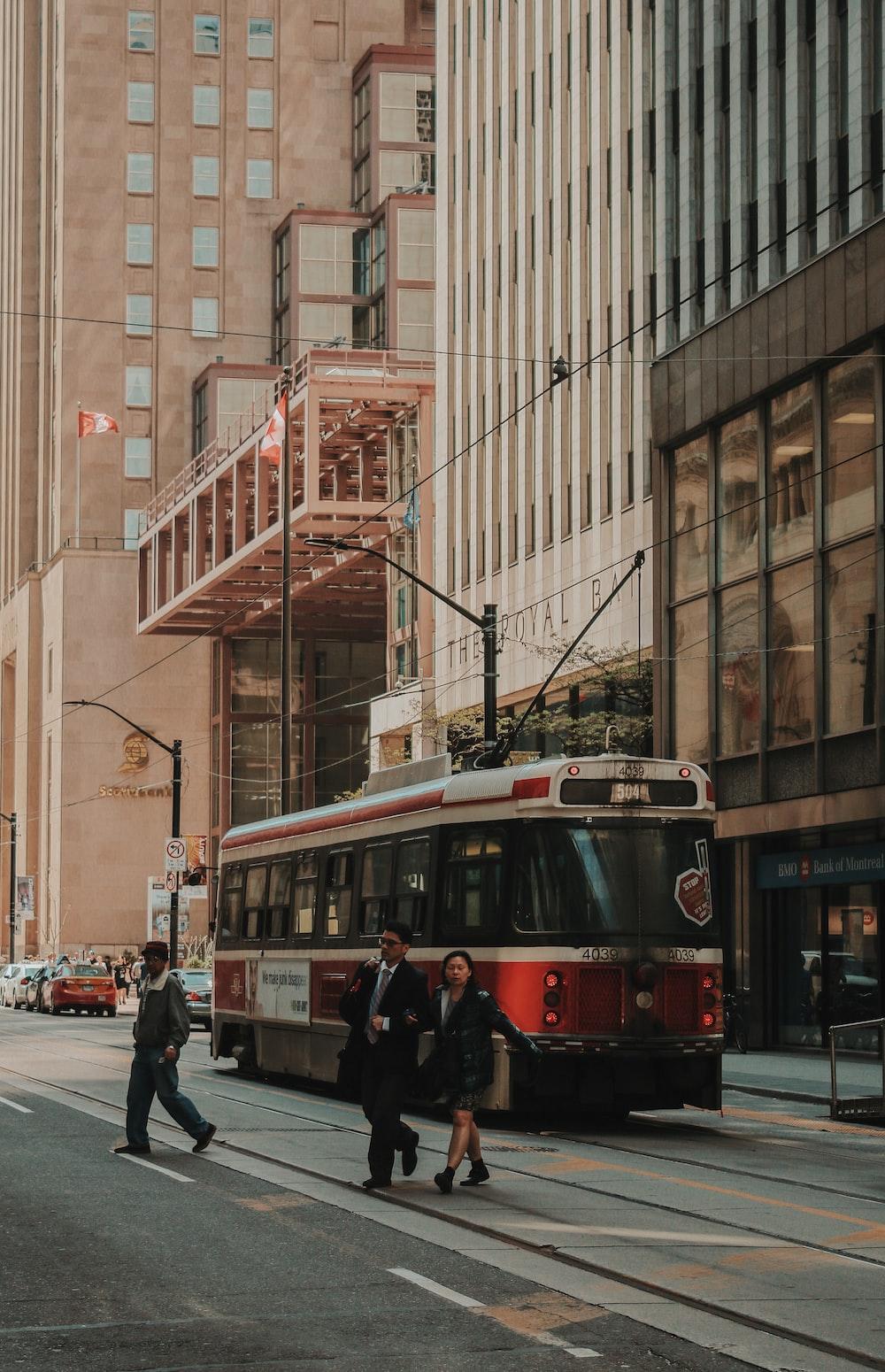 man and woman walking near city tram