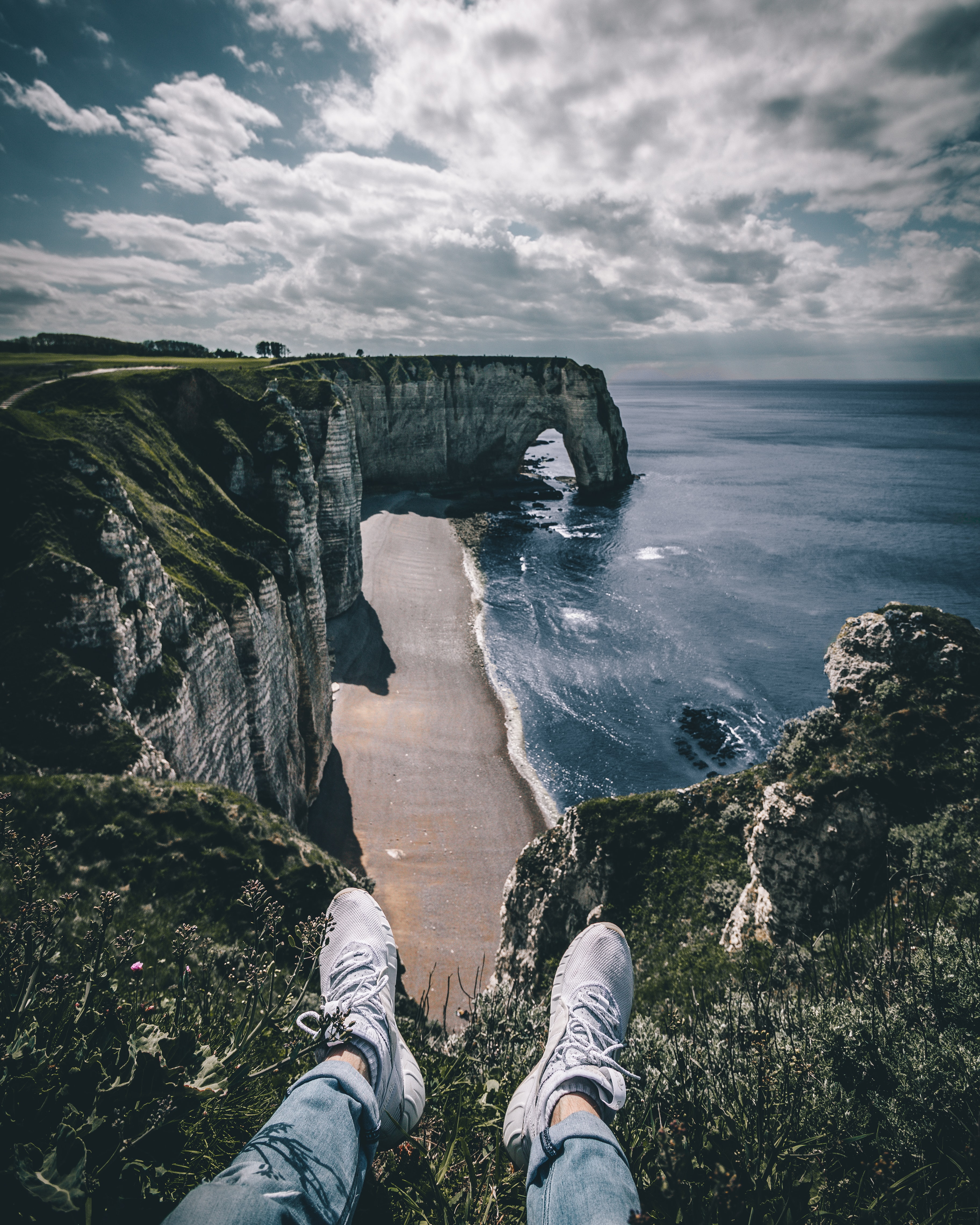person wearing white sneakers beside cliff