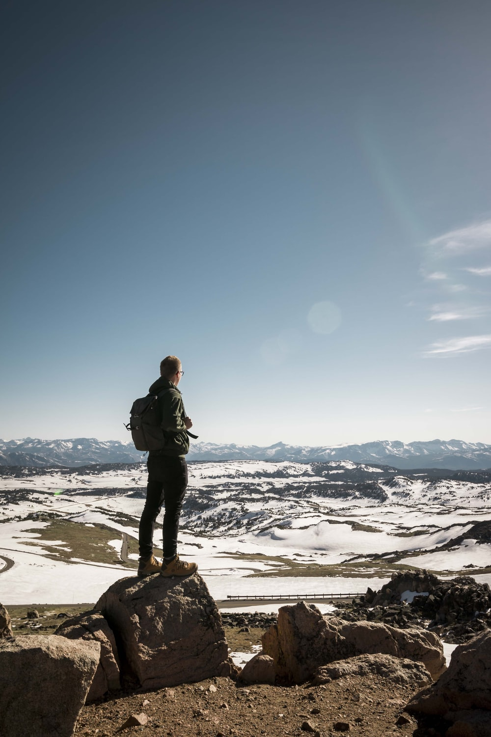 man standing on stone overlooking snow-capped mountain
