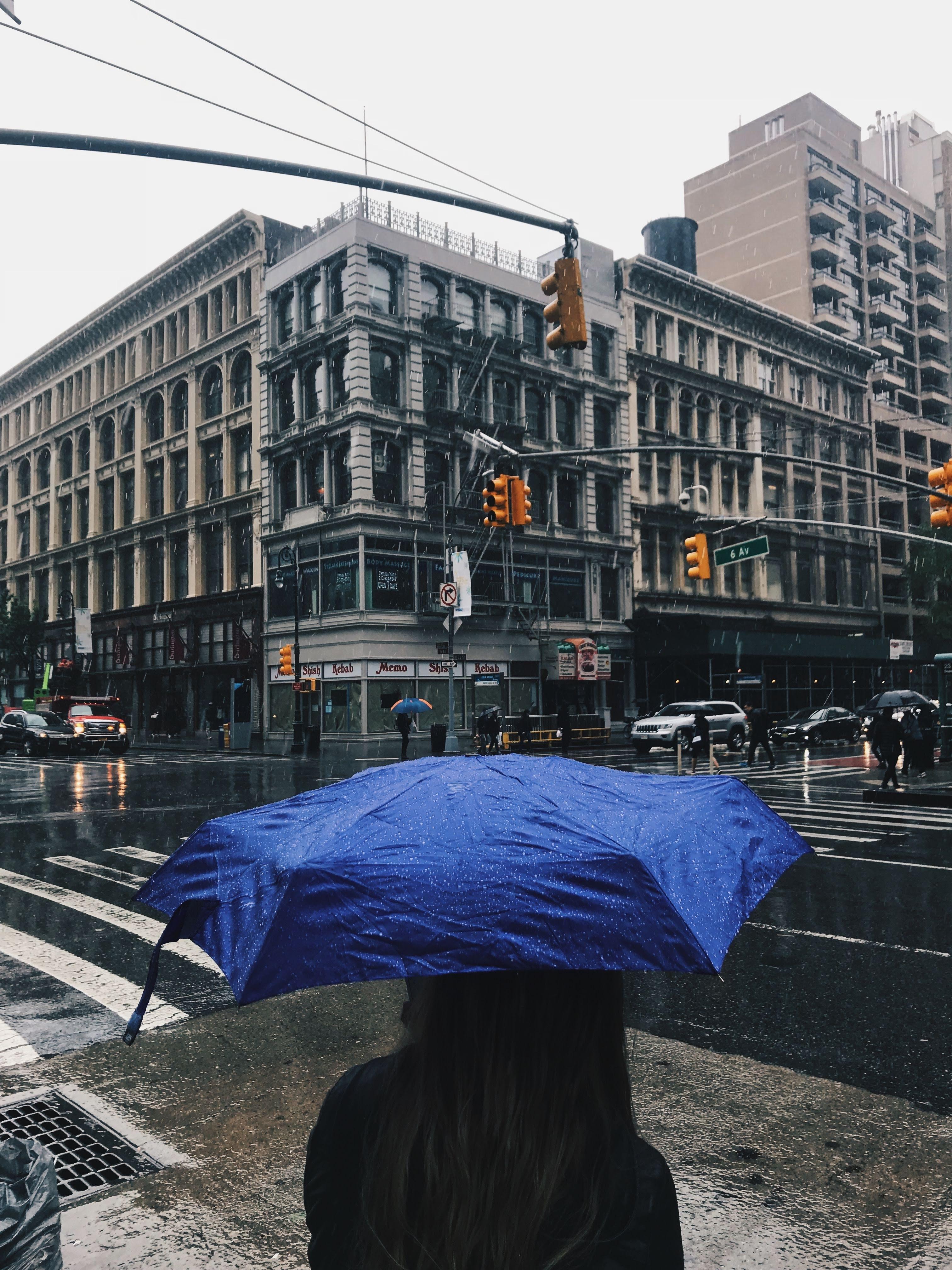 woman using umbrella looking at building