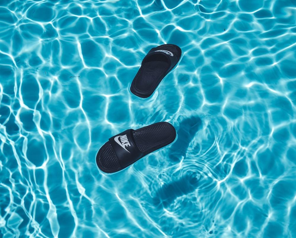 black Nike slide sandals on swimming pool