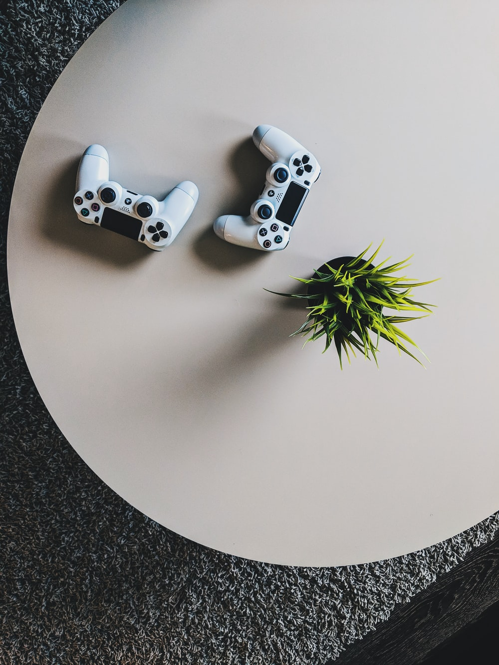 two Sony PS4 controllers on table