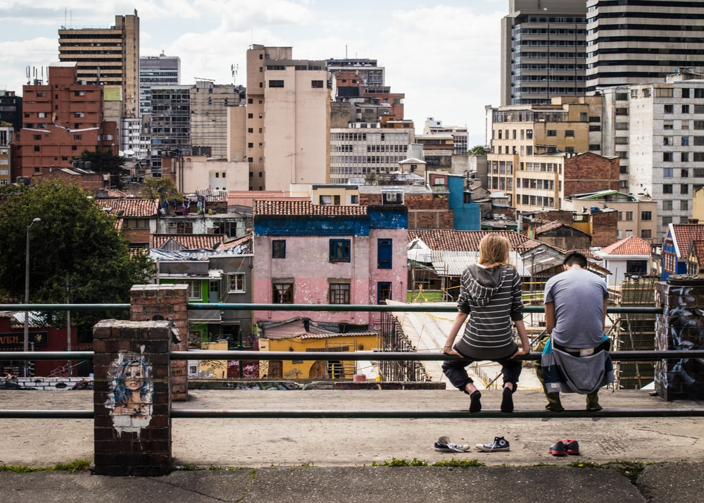 photo of two people sitting on pole fence facing high-rise building