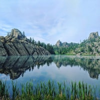 landscape photography of calm body of water surrounded by rocky mountains