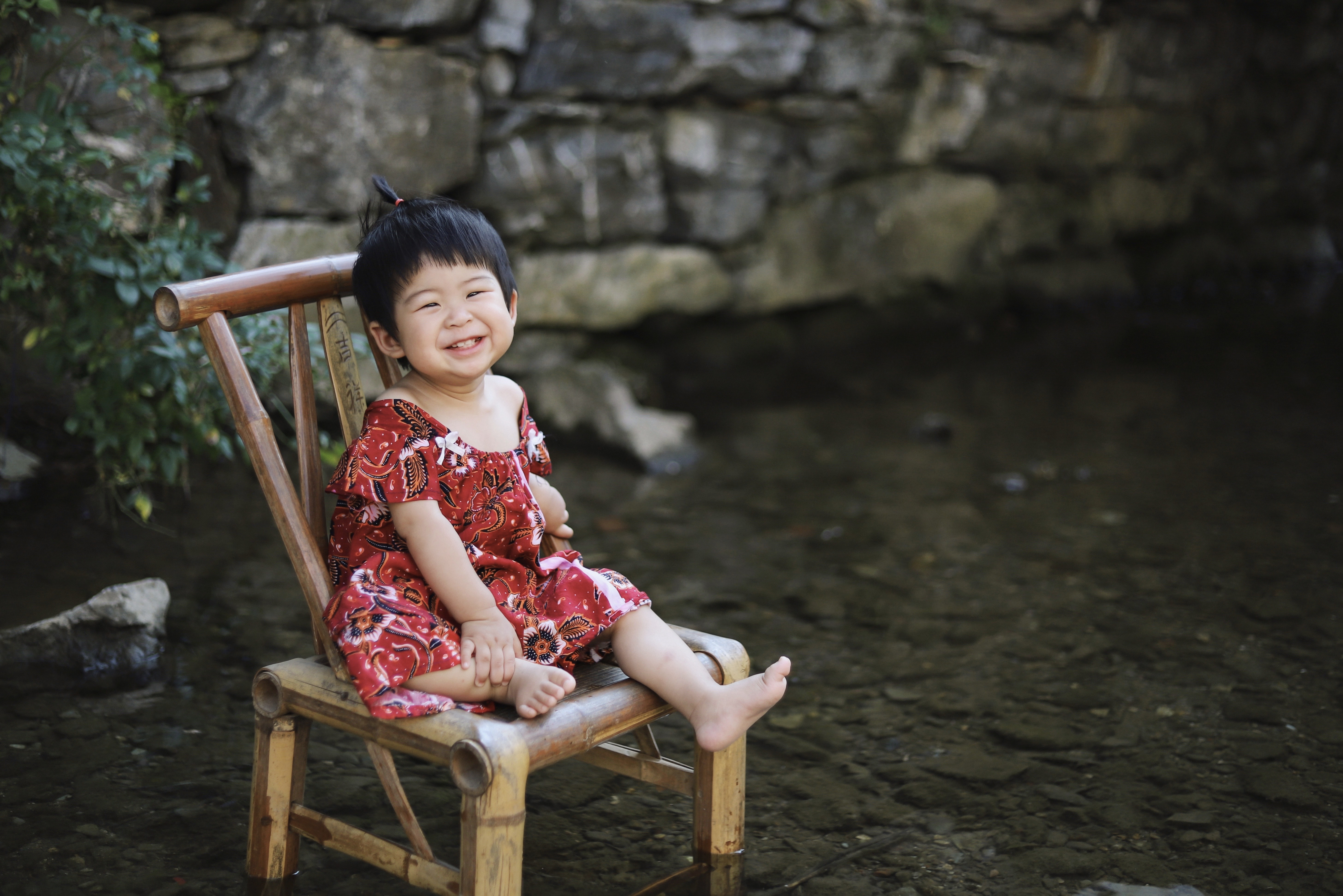 toddler sitting on brown wooden chair