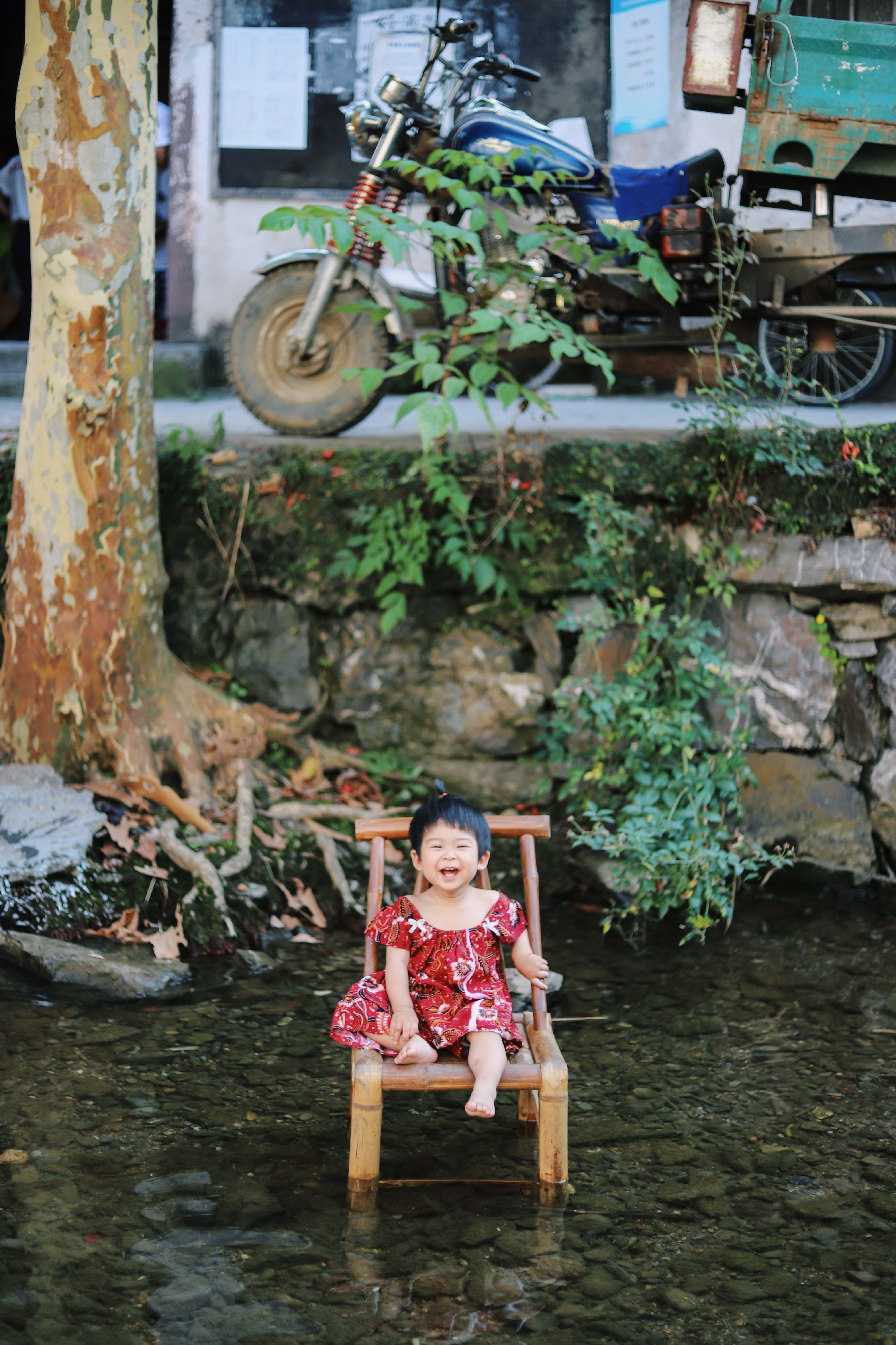 girl sitting on chair surrounded by body of water