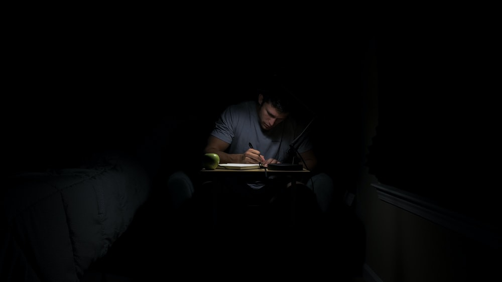 man writing in dark room