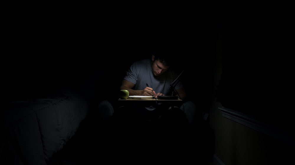man writing in dark room