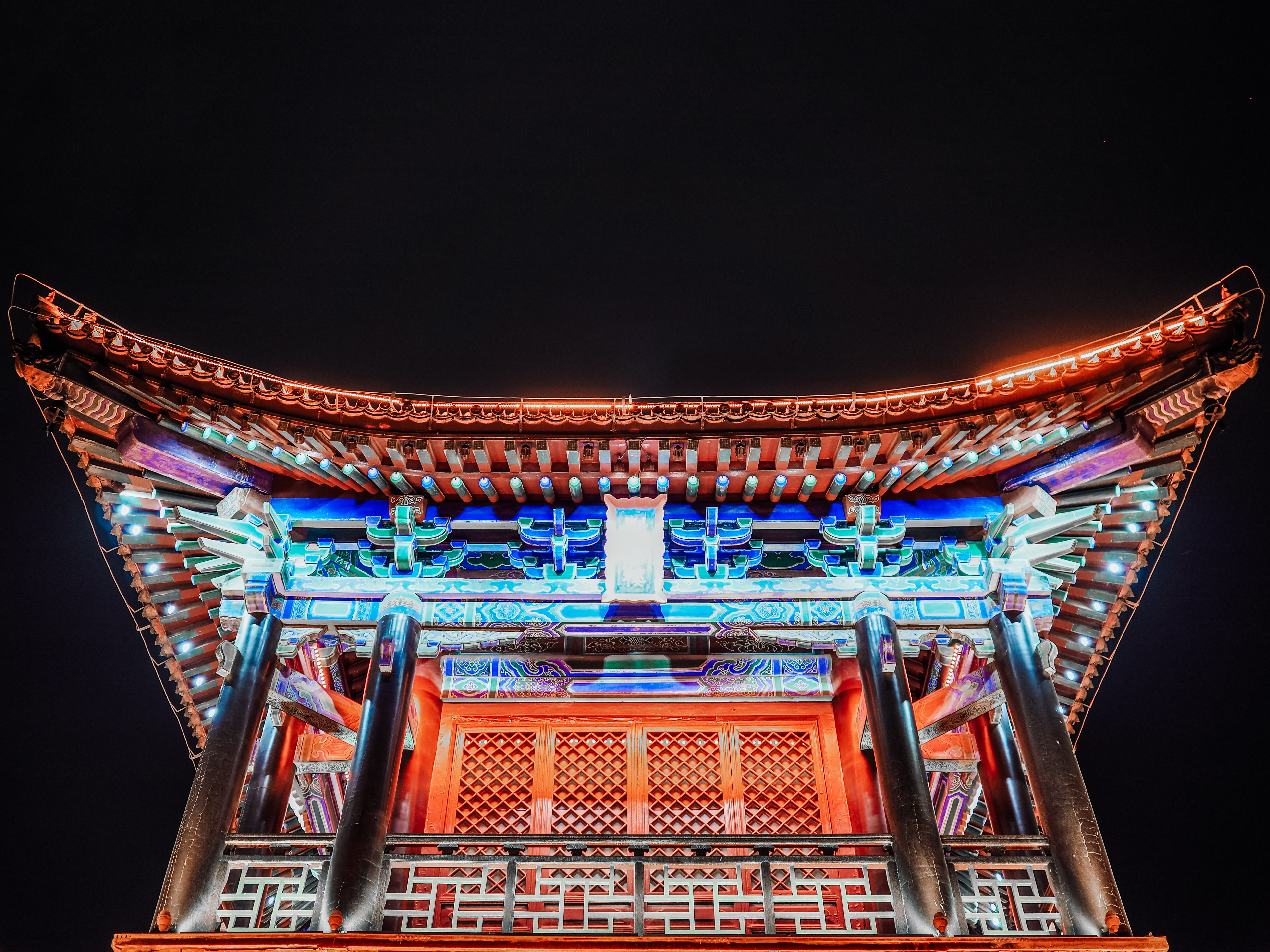 lighted orange and blue pagoda temple at night