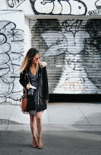 woman walking in street holding Android smartphone