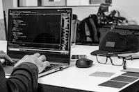 grayscale photo of man using laptop coding