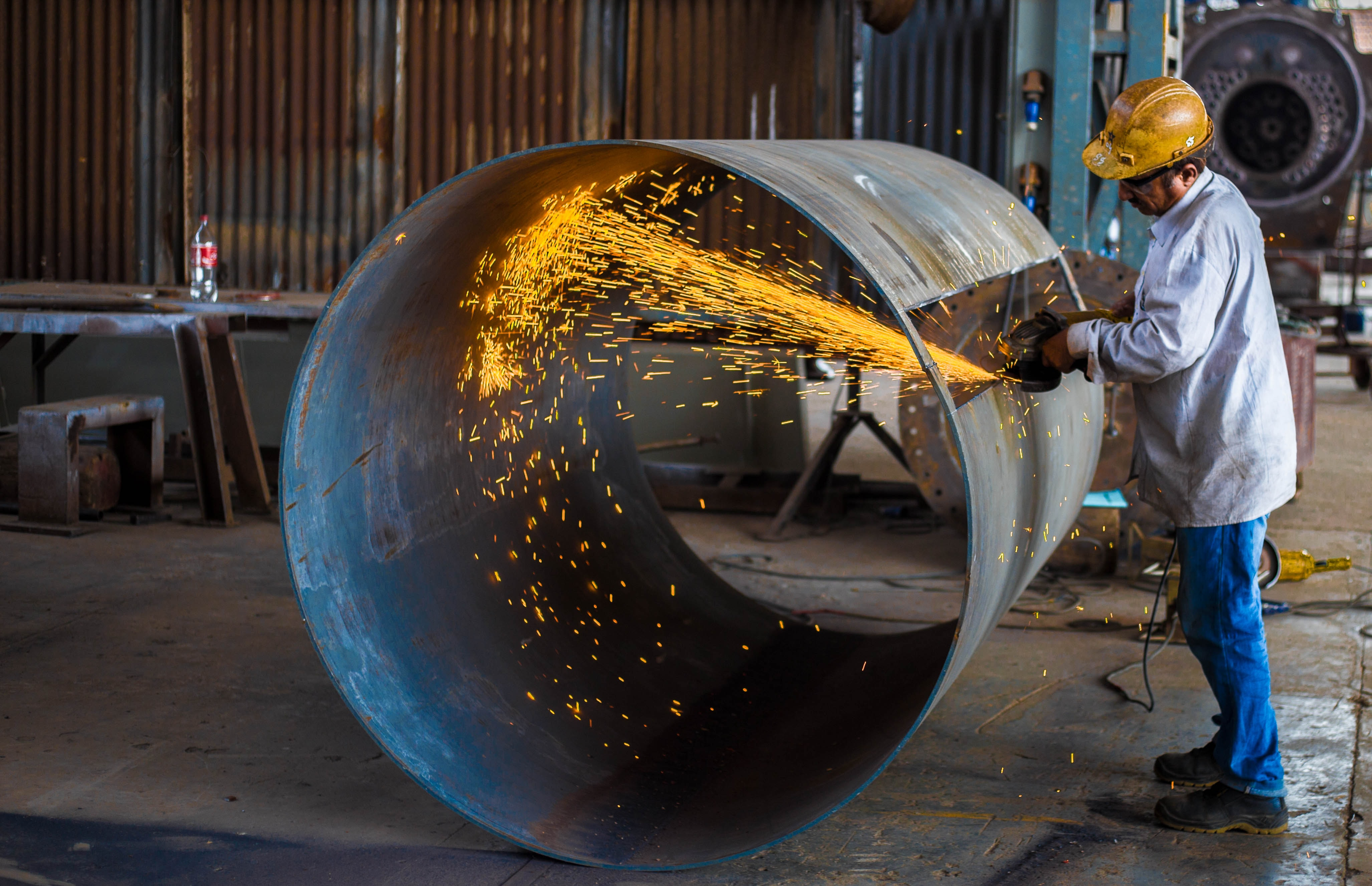 man wearing yellow hard hat holding angle grinder