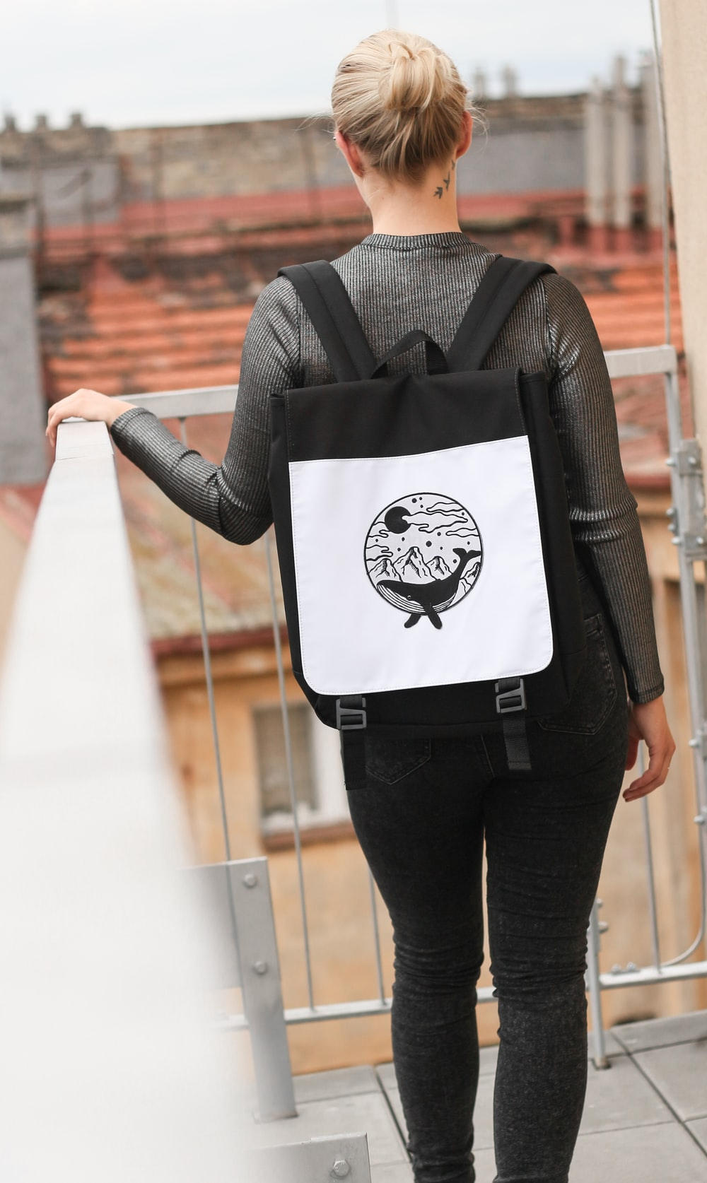 selective focus photography of woman wearing black and white backpack standing on terrace while holding handrails
