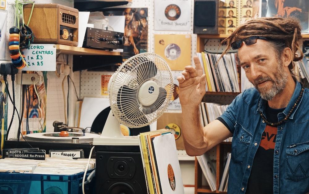 man beside white desk fan