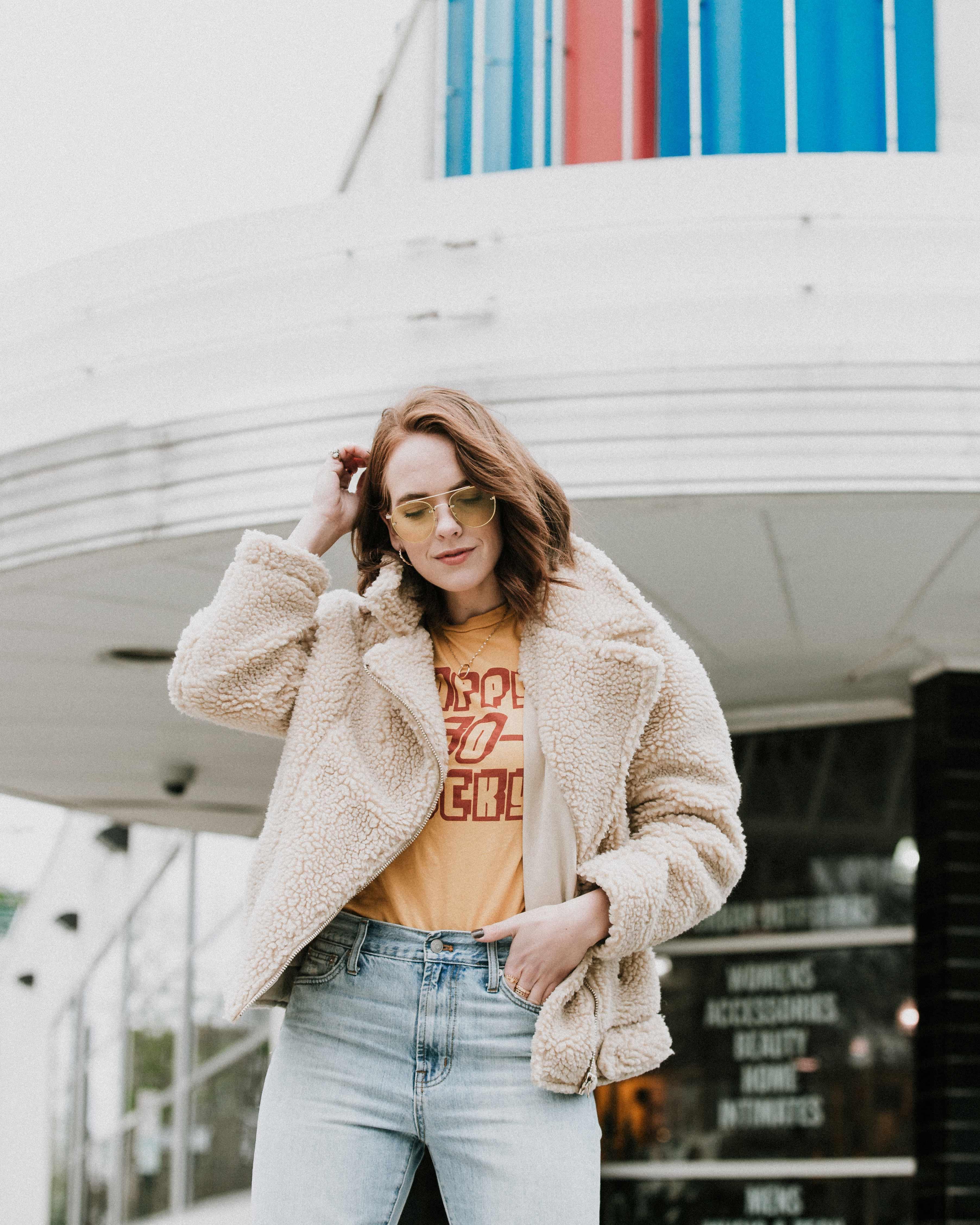 woman wearing brown fur jacket shriveling her hair ]