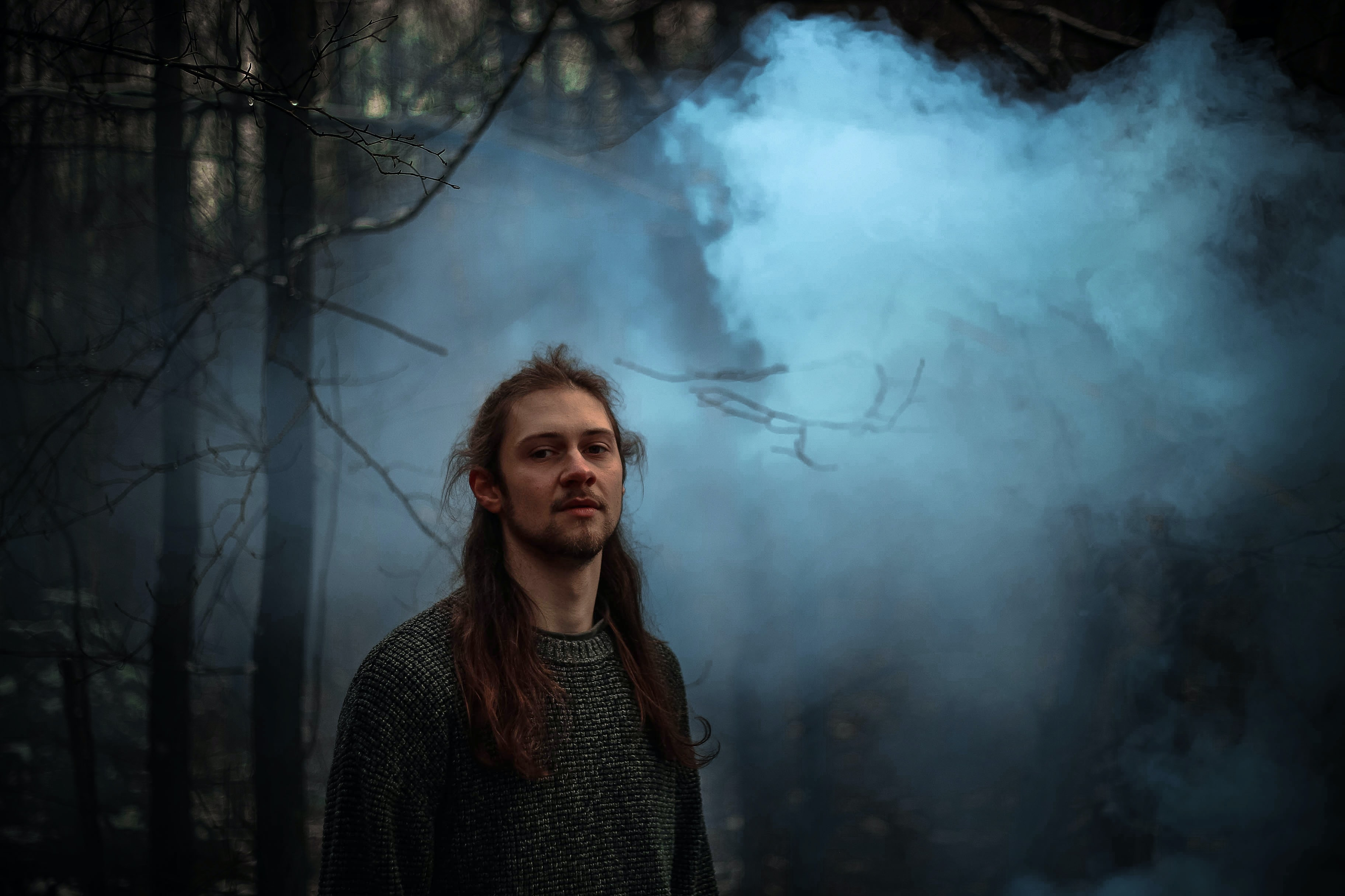 man in black top standing in foggy forest
