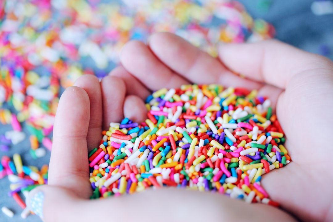 A young person holding rainbow colored candy sprinkles for decorating cakes, pastries, and ice cream.