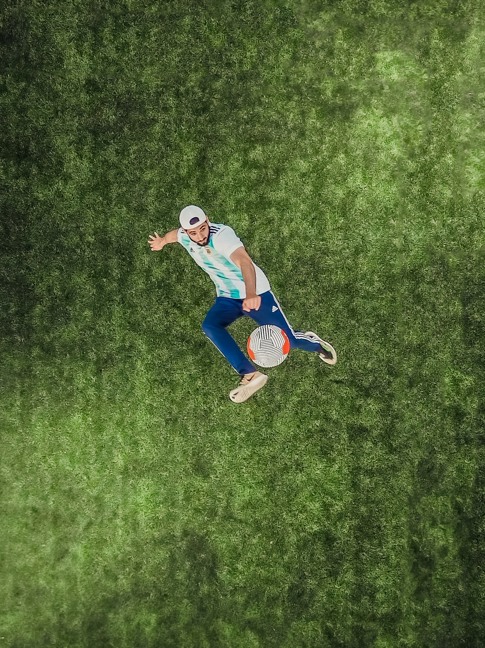 aerial view of man playing soccer ball on grass