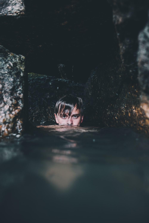 man near rock formation soaking on water