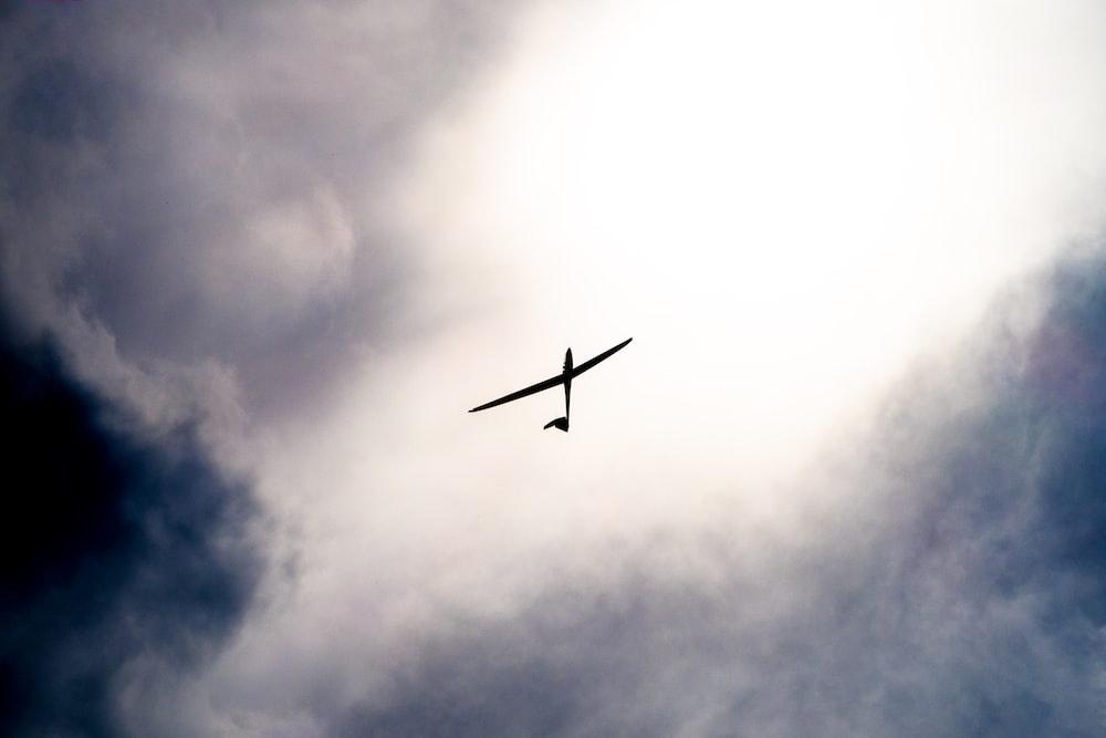 white toy plane under white sky