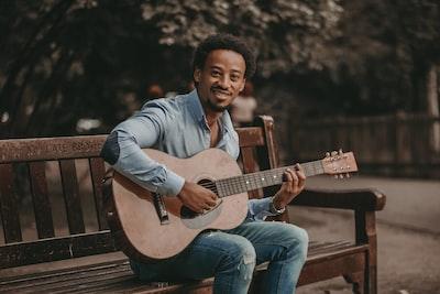 man sitting on bench playing guitar