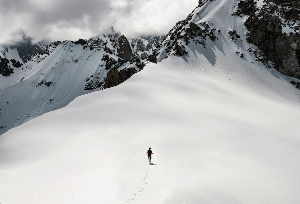 man climbing snow-covered mountain