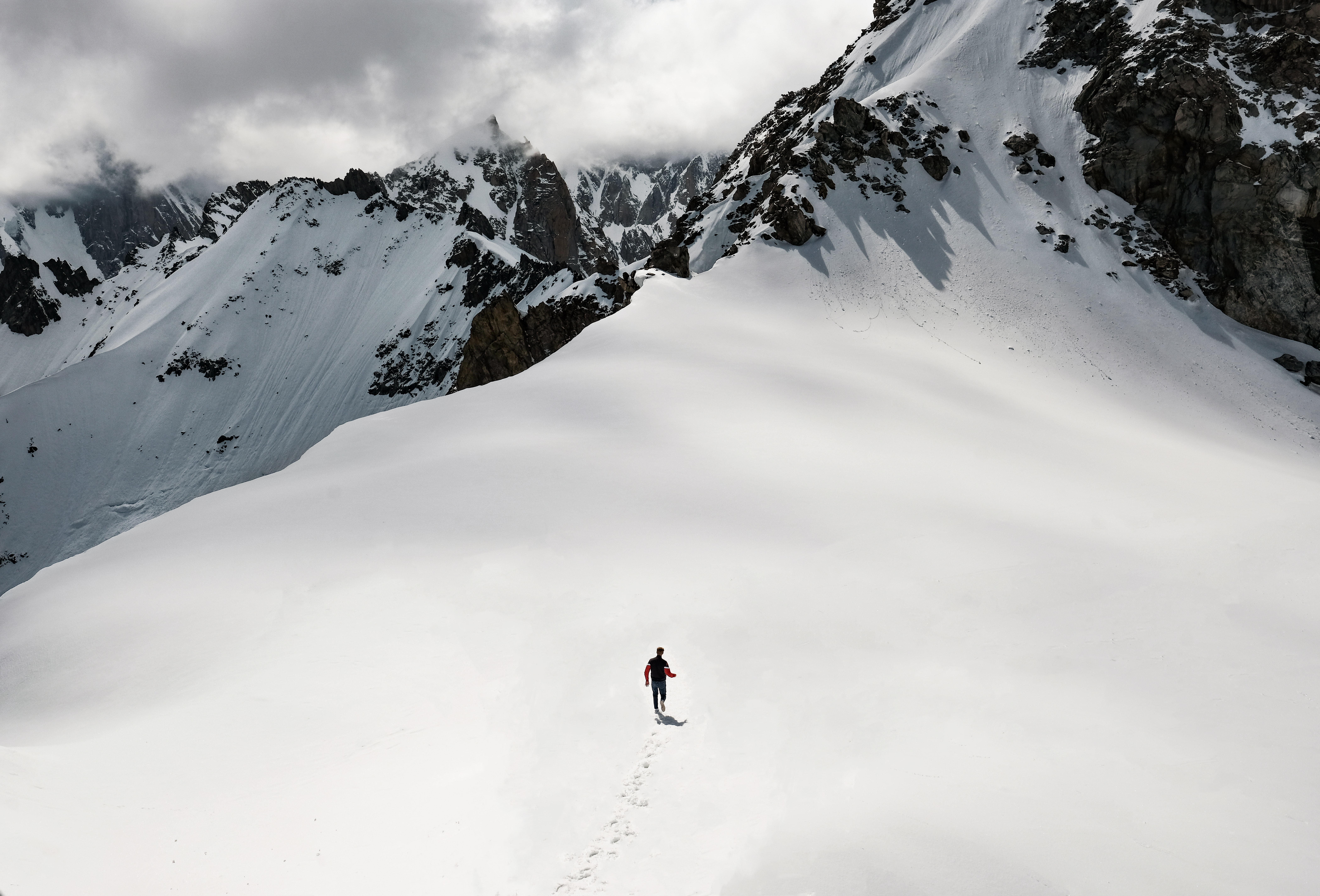 man climbing snow-covered mountain