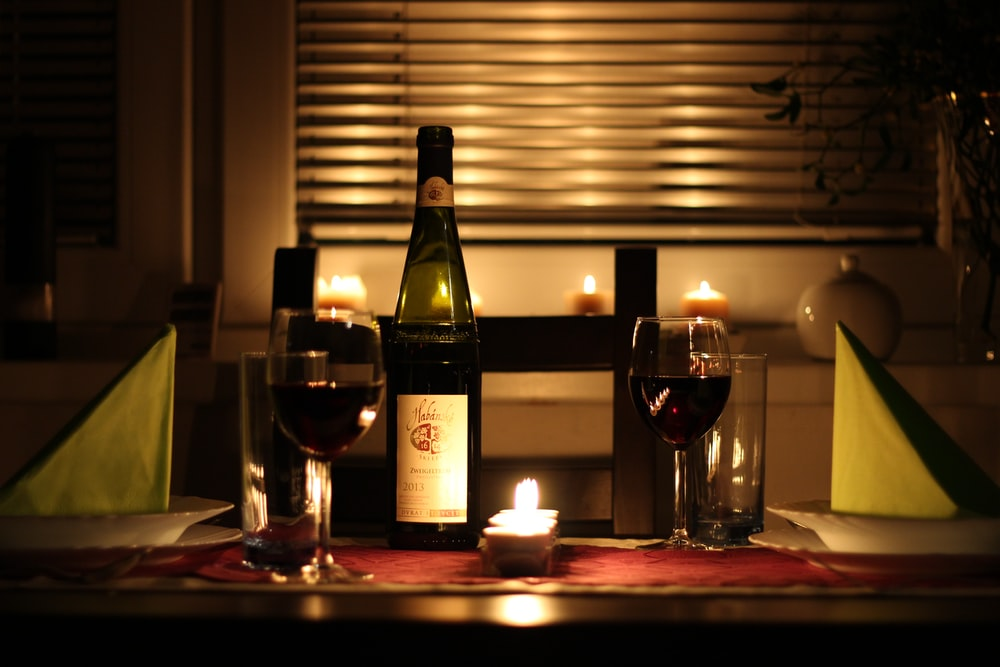 wine glass filled with wine beside bottle on table