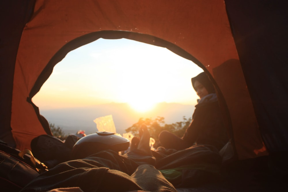 person lying inside camping tent at daytime