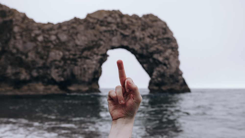person showing right middle finger on front of brown rock formation