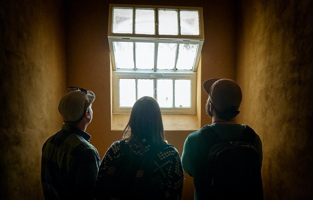 three people facing window
