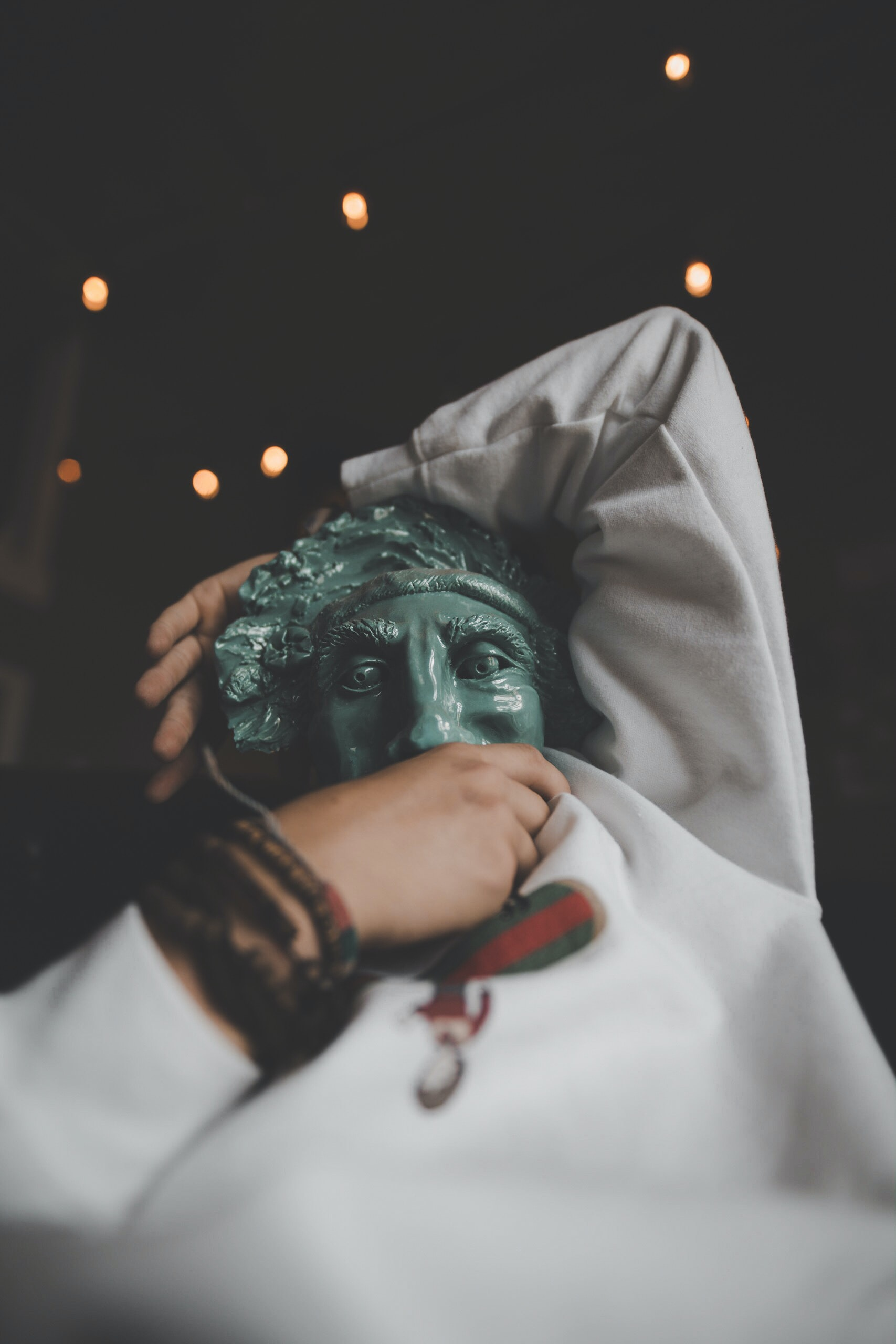 person holding green ceramic mask