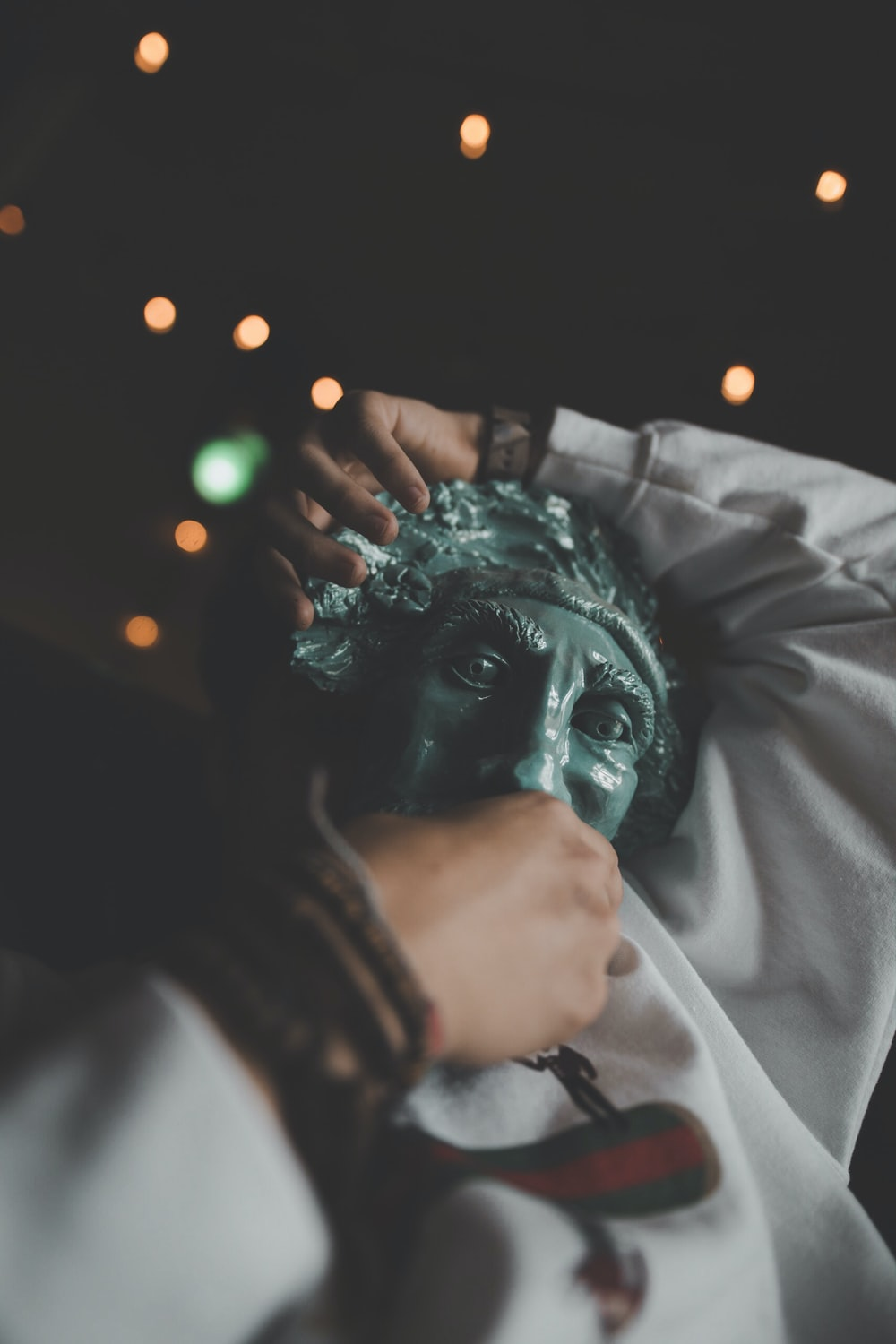 person holding green face mask outsidde