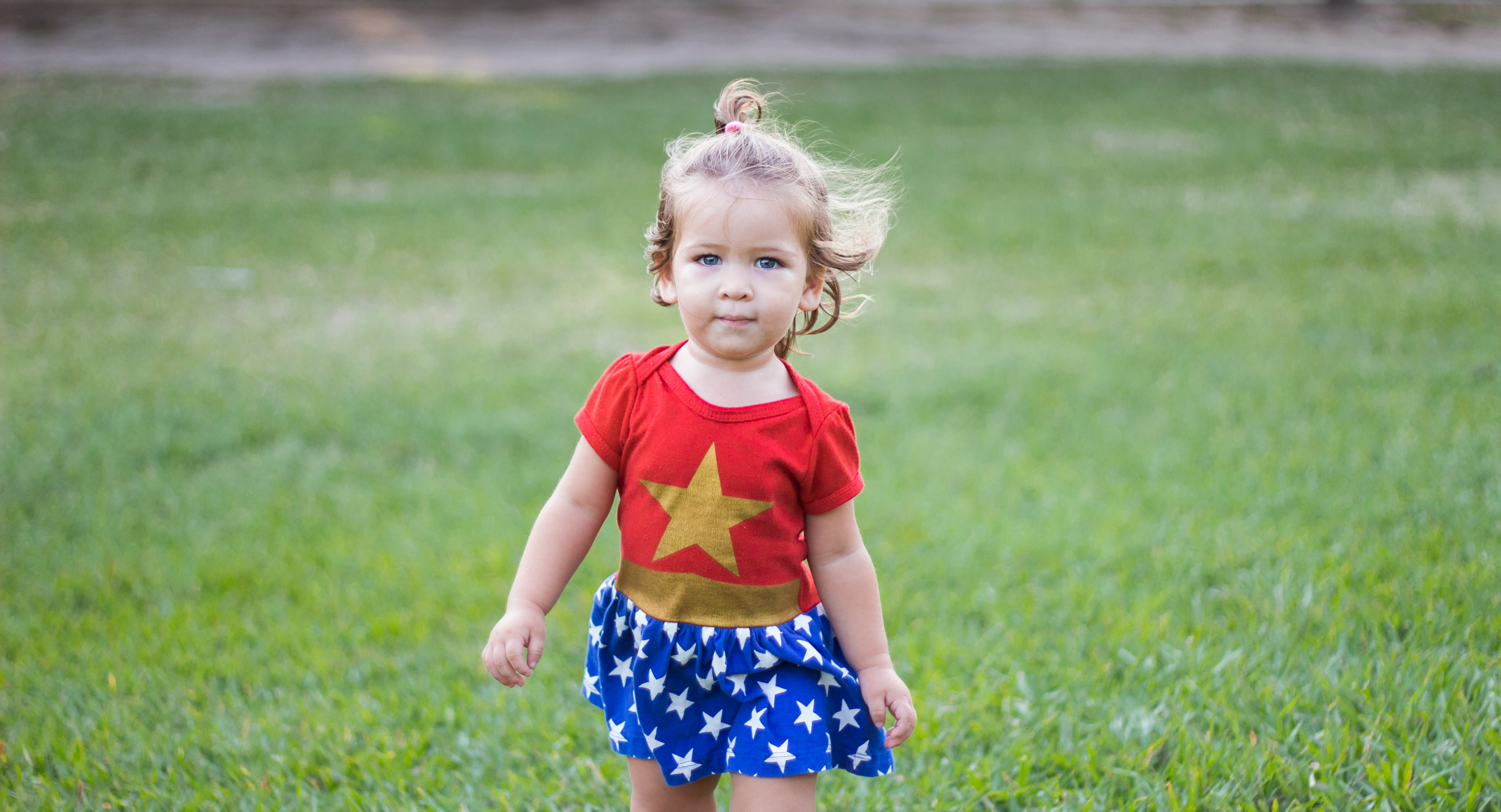 girl wearing Wonder Woman dress walking on green grass field during daytime