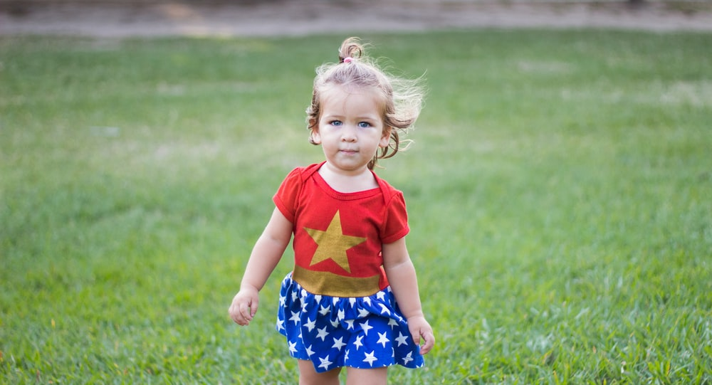 girl wearing Wonder Woman dress walking on green grass field during daytime