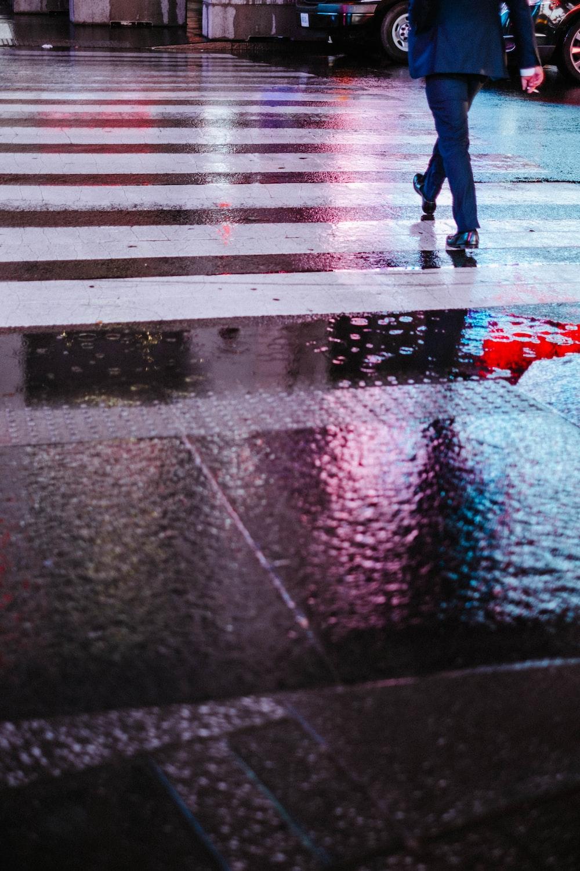 person wearing suit jacket walking on pedestrian lane