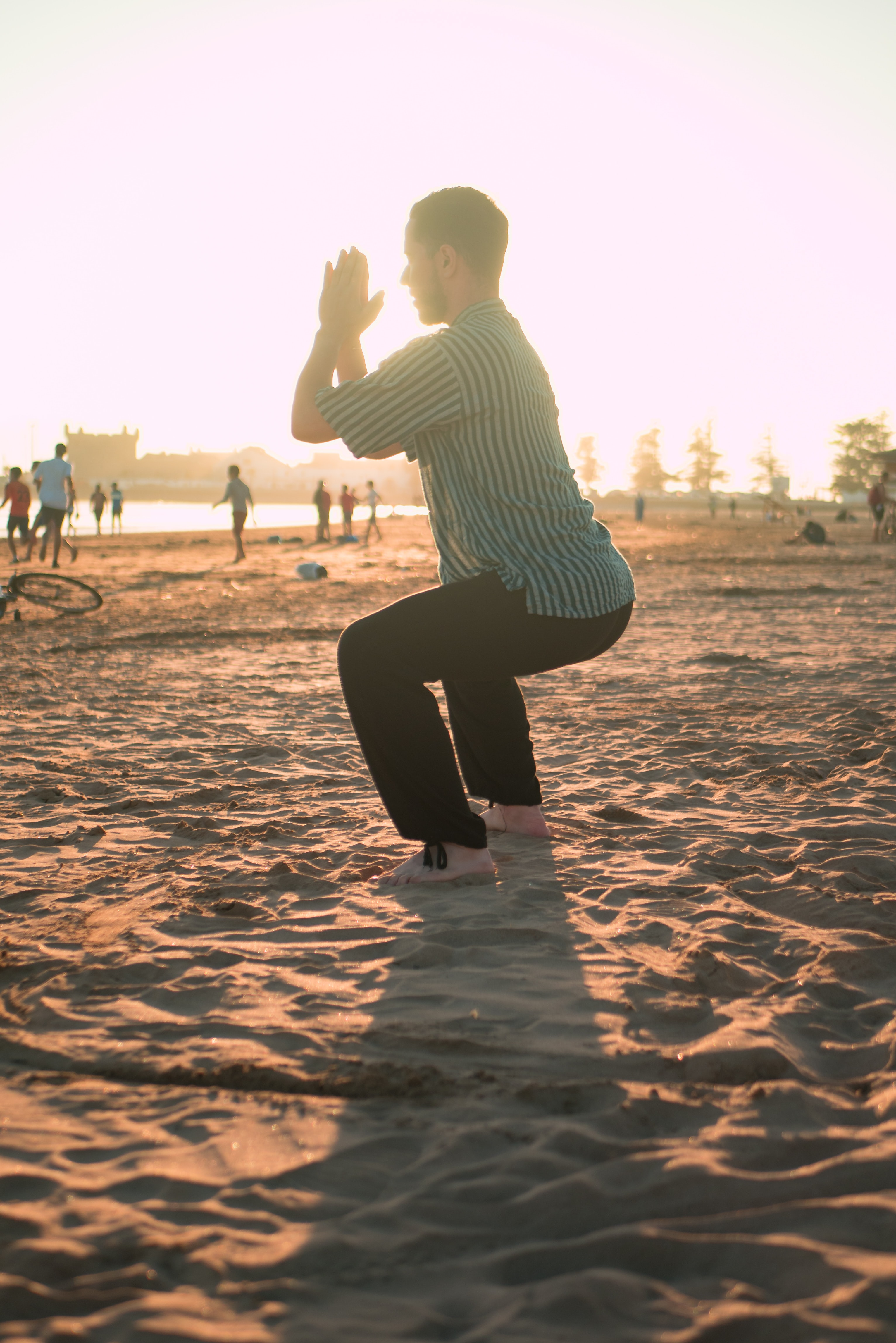 man closing his hands white squatting on sand