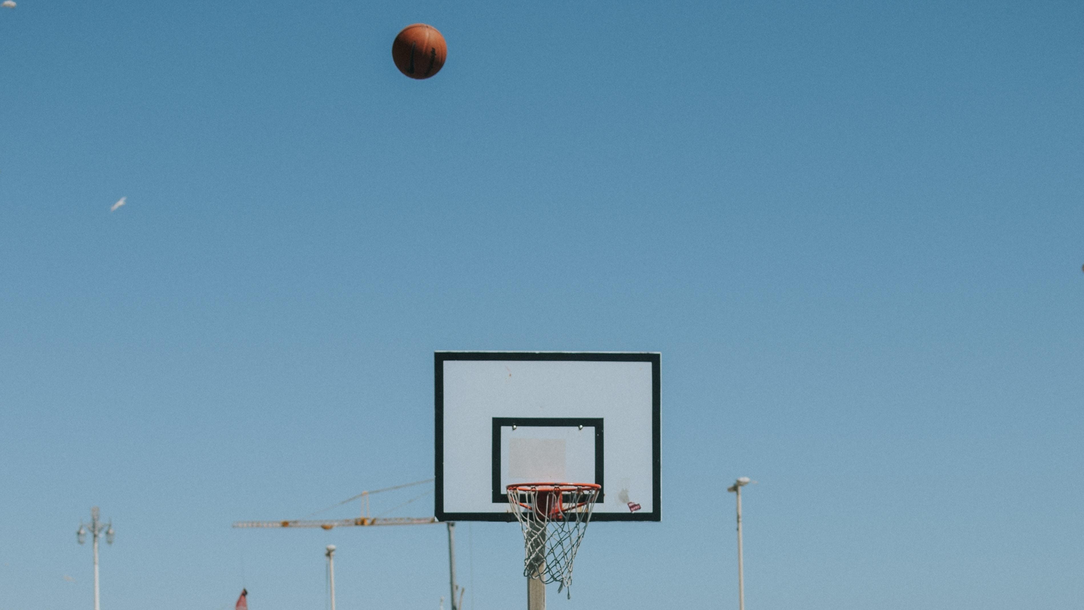 flying basketball and basketball hoop under blue sky during daytime