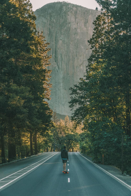 man standing on asphalt road between trees