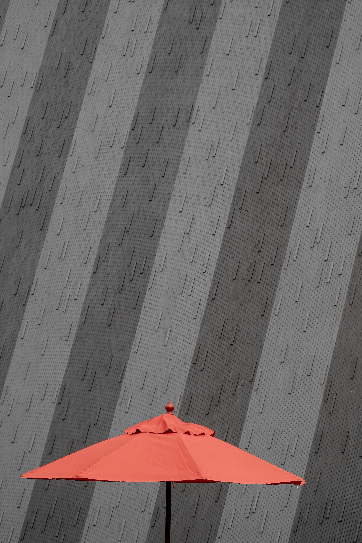 orange and black parasol near the gray wall