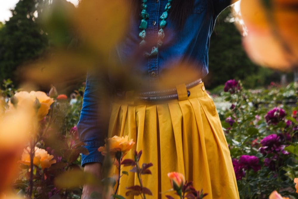 woman in yellow skirt and blue shirt standing on bed of flowers