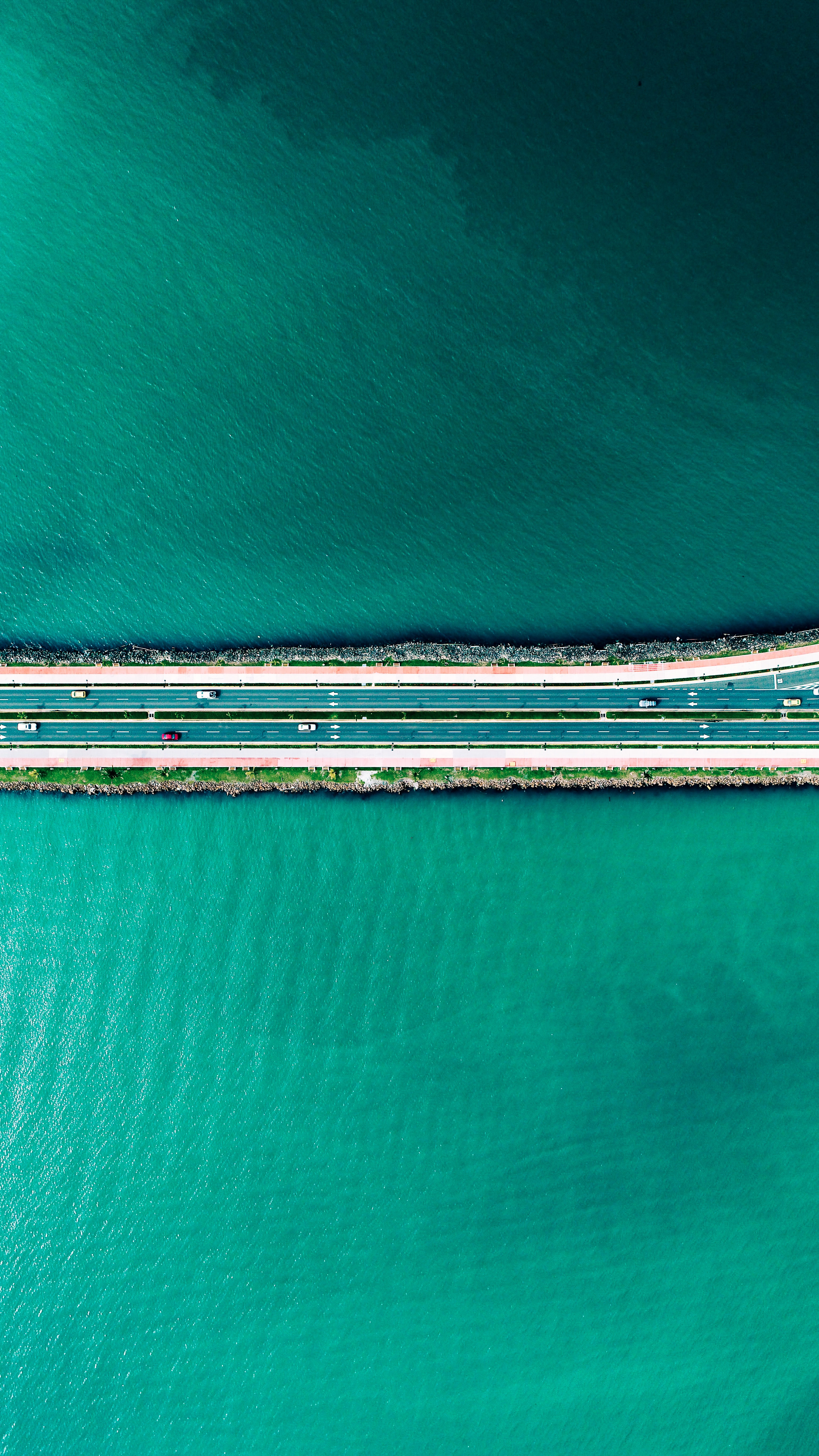 aerial photography of road between body of water