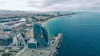 clear glass building near sea under grey sky barcelona zoom background