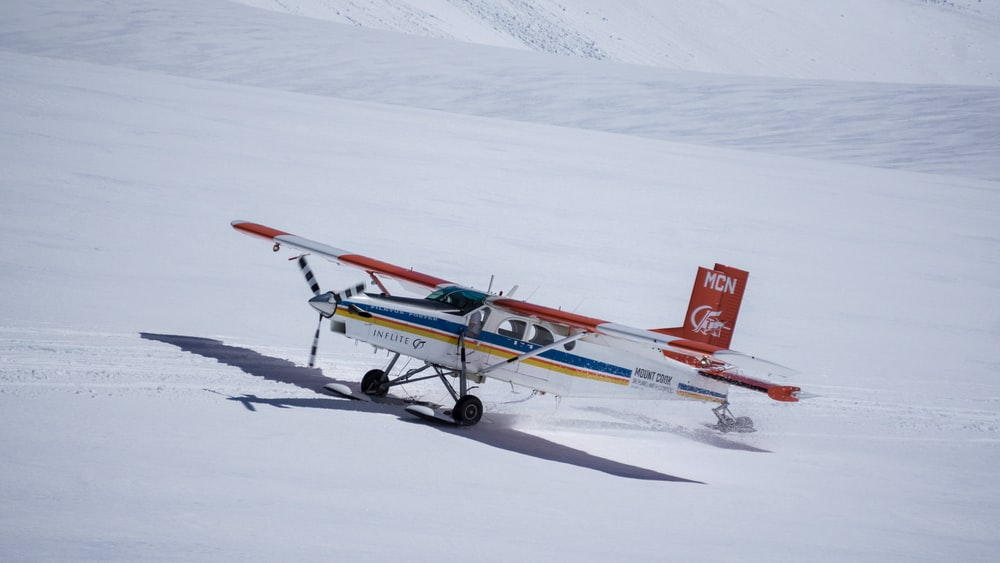 photo of white, blue, and red plane on white snow at daytime