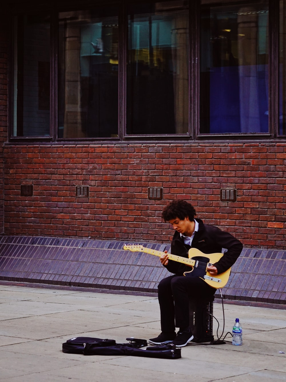 man playing with his electric guitar while sitting on guitar amlplifier